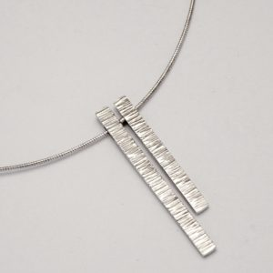 Close image of the two different length hammer textured lengths from the from, hanging from the curve of omega necklet